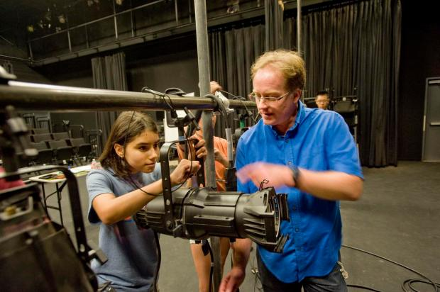 Student and Teach working on a stage light